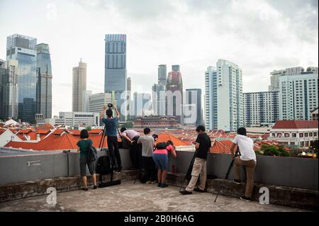 23.01.2020, Singapore, , Singapore - People stand on a roof and take pictures of the city view of Chinatown and the skyline with the skyscrapers in th