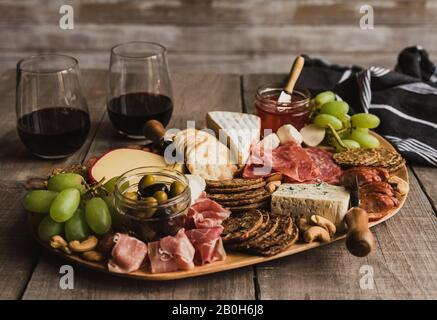 Close up of charcuterie board and glasses of wine on wooden table. - Stock Photo