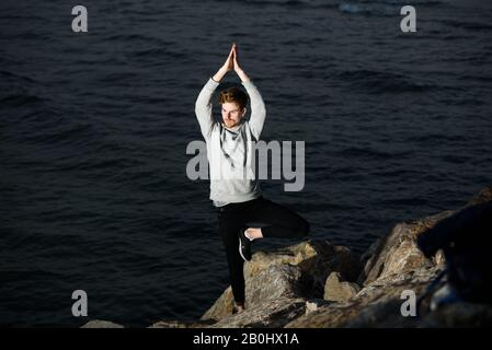 Young redhead practicing yoga, Vriksasana tree posture, to concentrate and help him with his mindfullness - Stock Photo