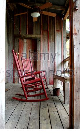 Red swing chair on old veranda in a traditional framhouse / Texas / USA - Stock Photo
