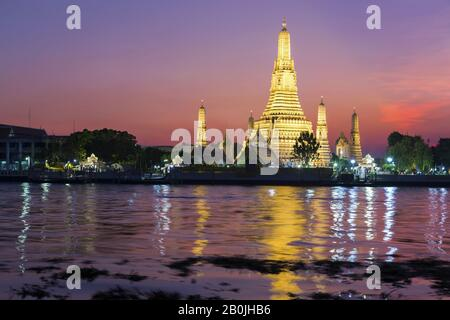 Dramatic Sunset Sky Colors over Wat Arun Temple or Temple of Dawn Buddhist Monument Reflected in Chao Phraya River in Bangkok, Thailand