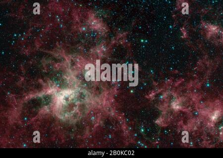 Washington, United States. 20th Feb, 2020. This image from NASA's Spitzer Space Telescope shows the Tarantula Nebula in three wavelengths of infrared light, each represented by a different color. The Tarantula Nebula was one of the first targets studied by the infrared observatory after its launch in 2003, and the telescope has revisited it many times since. Now that Spitzer was retired on January 30, 2020, scientists have generated a new view of the nebula from Spitzer data. NASA/UPI Credit: UPI/Alamy Live News - Stock Photo