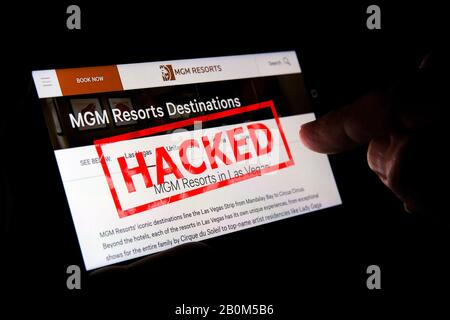 MGM website on the smartphone screen with a red stamp HACKED on top and finger pointing at it. Concept. Editorial illustrative. - Stock Photo