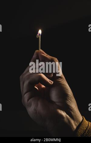 The hand of an adult man holding a burning match - Stock Photo