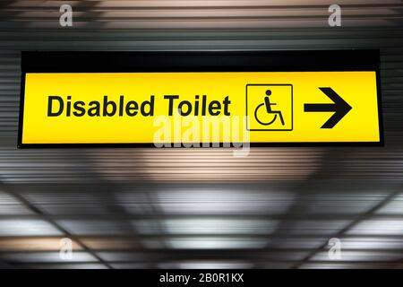 sign with arrow point to disabled toilet at the airport for passenger with impaired body. universal design for elderly or the disabled in public place - Stock Photo