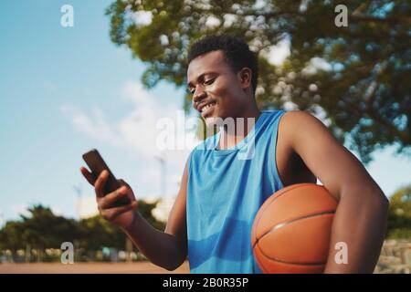 Portrait of a smiling young male basketball player holding ball in hand texting messages on his smart phone at park