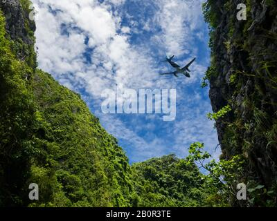 Airplane taking off , fly over the mountain view. Silhouette of a big passenger or cargo aircraft, airline on cloudy blue sky. Transportation , vacati - Stock Photo