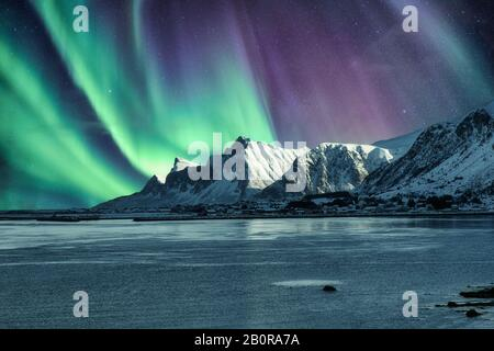 Aurora Borealis, Northern Lights Above of snowy mountain in Lofoten Islands at Norway - Stock Photo