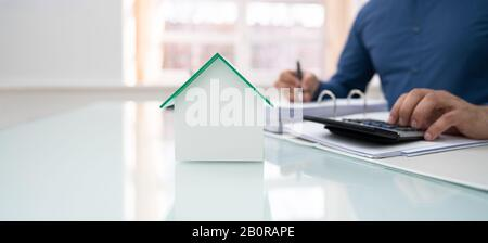 Midsection Of Businessman Calculating Invoice With House Model In Office - Stock Photo