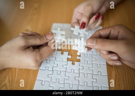 Man hands connecting couple puzzle piece in office. Business solutions, target, successful, goals and strategy concepts