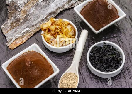 Set of traditional Japanese ingredient for cooking basic dashi broth. Algae kombu and wakame, miso paste, katsuobushi and dry granules. Black ceramic