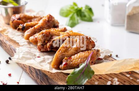 Grilled chicken wings are located on a wooden board, Selective focus - Stock Photo