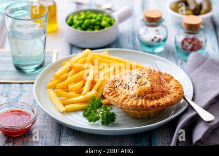 Meat pie with french fries on a white plate. Wooden background. Close up. - Stock Photo