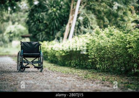 Empty wheelchair parked in park, Health care concept. - Stock Photo