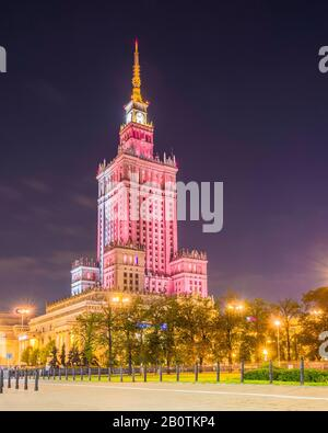 Illuminated at night, the Palace of Culture and Science (1955) is a Soviet designed skyscraper in central Warsaw, Poland. - Stock Photo