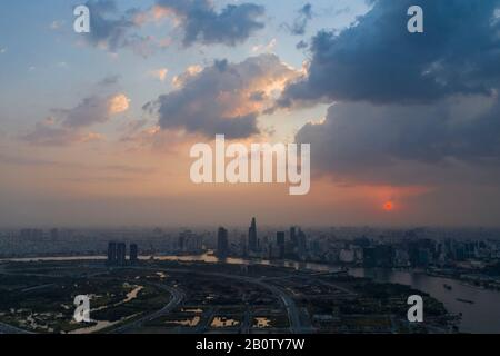 Dramatic aerial view of Saigon river and Ho Chi Minh City skyline at sunset with beautiful stormy and brightly colored clouds in the sky