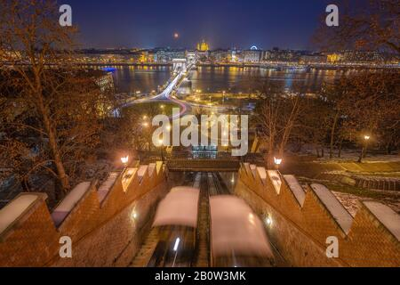 Budapest, Hungary - View from the Buda Castle Hill at blue hour with moving funiculars, Szechenyi Chain Bridge, St. Stephen's Basilica and blood Moon - Stock Photo