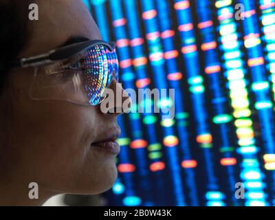 Genetic Research, female scientist viewing a DNA profile of a human sample on a screen in the lab.