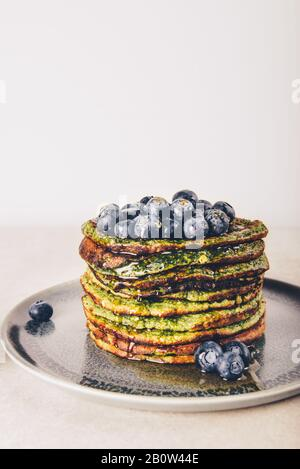 Healthy easy blender green pancakes made from spinach, coconut milk, banana and oats with blueberries. Vegetarian and gluten free breakfast - Stock Photo