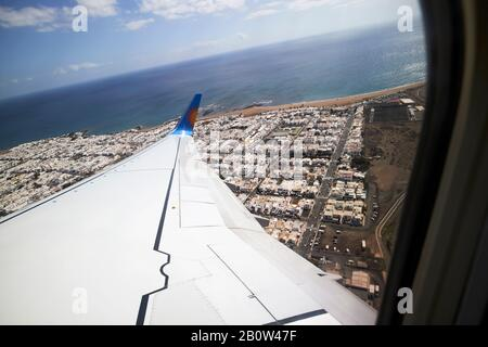 looking out of window of jet2 aircraft taking off from arricife airport in lanzarote flying over densely packed playa honda