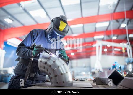Welder spot welding pipe bend in metal fabrication factory. - Stock Photo