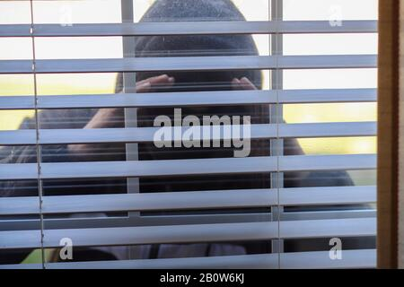 A burglar wearing a black hoodie and a mask attempting to  break in  a house - Stock Photo