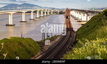 Benicia in California, rusty ole bridge & train tracks, a great juxtaposition of old vs new. - Stock Photo