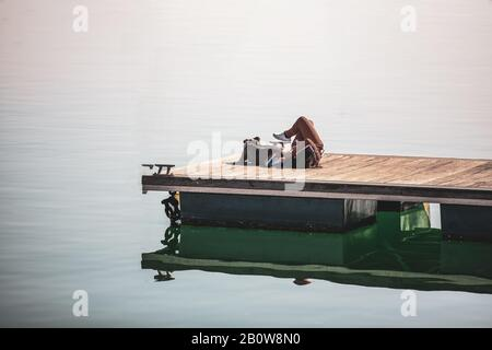 Girl lying next to her pit bull breed dog on the wooden pier of a harbor - Stock Photo