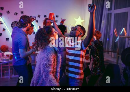 Group of young people spending funny time they dancing and enjoying the music during a party - Stock Photo