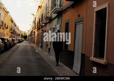 Full body male figure, back to camera. Wearing a hat, Unrecognizable silhouette in a Spanish alley with a row of cars on the left and a little oran - Stock Photo