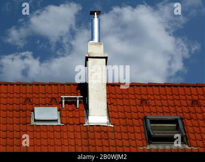 modern brown stucco chimneys with white ceramic cap stone, bright brown red clay tile roof tiles and clay vents. clear blue sky. construction concept - Stock Photo