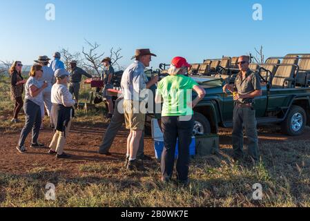 KwaZulu-Natale, Zululand, South Africa--January 14, 2018.  Tourists on Safari stop for cocktails--sundowners--as the sun begins to set over the Africa - Stock Photo