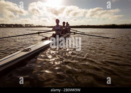 Teammates rowing on the water - Stock Photo