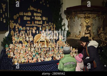 Young visitors observe the traditional gingerbread nativity scene (perníkový betlém) displayed in Saint Matthias Church (Kostel svatého Matěje) in Dejvice district in Prague, Czech Republic. Gingerbread figures of the nativity scene are baked annually in the church in the Christmas season. - Stock Photo