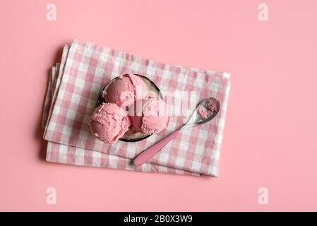 Raspberry ice cream in a glass bowl on napkin, on pink seamless background. Above view of berries ice cream.  Homemade red ice cream. Summer dessert. - Stock Photo