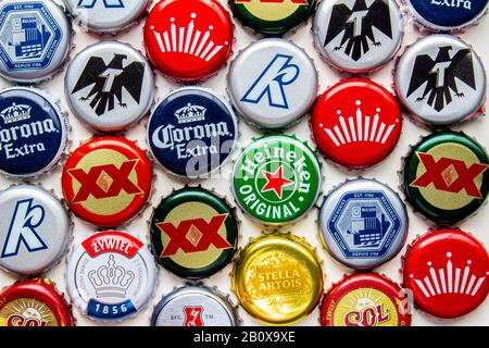 Calgary, Alberta, Canada. Feb 21 2020. Several beer bottle caps on a white background. Corona, Stella, Budweiser, DosEquis, Molson, Sol, Tecate, Kokan - Stock Photo