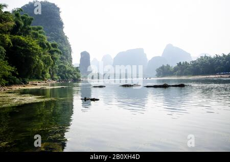 A view along the banks of the Li River, Yangshuo, Guilin, China. With bamboo forests on either side and distant mountains fading into the mist. - Stock Photo