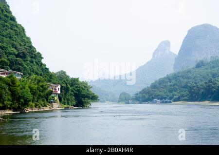 The Li River at Yangshuo, Guilin, China, with a house, distant buildings and karst mountains hiding in the mist on the horizon - Stock Photo