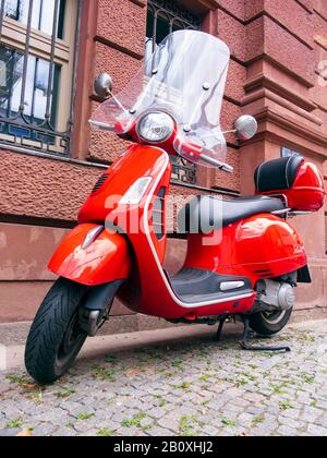 Berlin, Germany - August 13, 2019: A red Vespa stands on the edge of the road in Berlin - Stock Photo