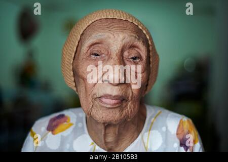 Portrait of an elderly Malay woman looking into camera - Stock Photo