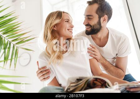 Happy young couple in love relaxing on a couch at the living room, rading magazine, laughing - Stock Photo