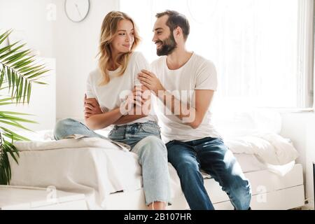 Lovely young couple in love relaxing on a couch at the living room, rading magazine, embracing - Stock Photo