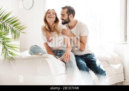 Happy young couple in love relaxing on a couch at the living room, rading magazine, embracing - Stock Photo