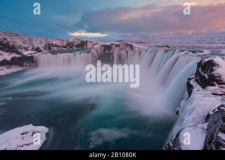 Evening light over Godafoss waterfall with ice and snow in winter, highlands, Iceland - Stock Photo