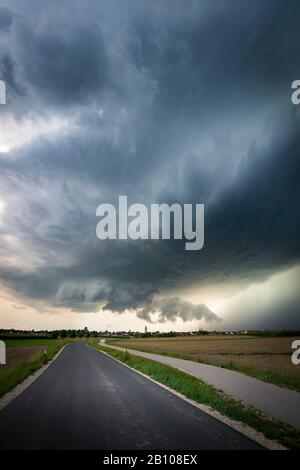 Low-hanging wall cloud, healthy updraft base and heavy precipitation core of a classic supercell over a country road near Heilsbronn, Bavaria, Germany Stock Photo
