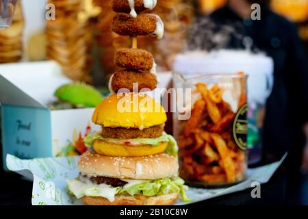 panning shot of a green vegetarian vegan burger, nachos drink with straw and potato twister with out of focus people in the background - Stock Photo