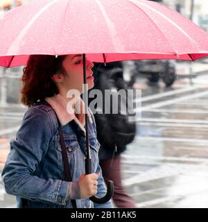 Belgrade, Serbia - September 24, 2019: One young woman in denim jacket walking under red umbrella on a rainy day - Stock Photo