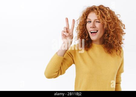 Cheeky good-looking redhead curly woman satisfied with her new look after hair and cosmetology salon, showing peace, victory sign, wink sassy and - Stock Photo
