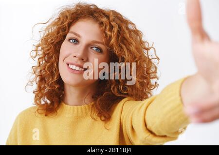 close-up-attractive-happy-smiling-redhead-woman-with-curly-hair-pulling-hand-forward-as-holding-smartphone-taking-selfie-on-camera-grinning-2b11bj4 Where to find a Bride On line