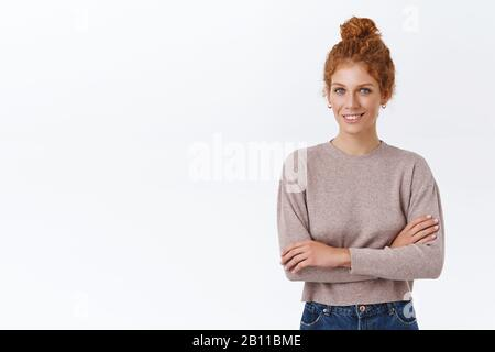 Confident, good-looking bossy female entrepreneur with red curly hair in stylish sweater, cross arms over chest, smiling pleased and interested, hear - Stock Photo